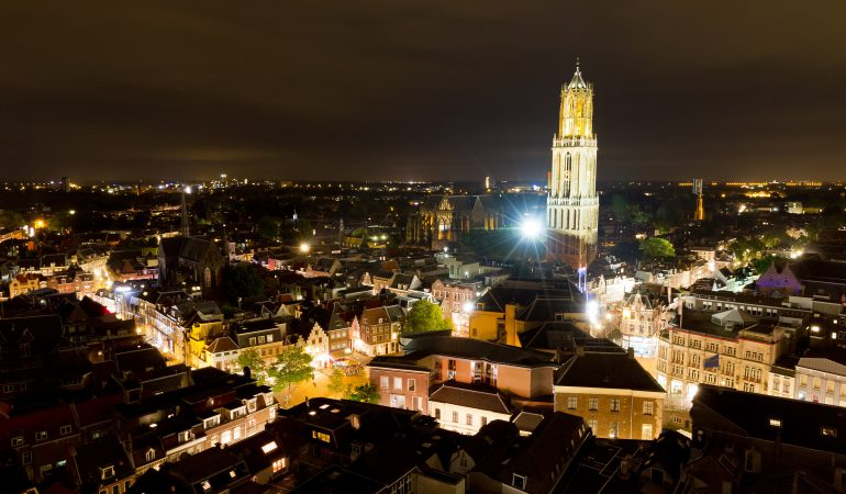 Cityscape of the city of Utrecht at night with the Dom cathedral lit by big lights